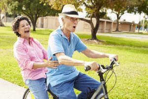 Seniors riding bikes in park showing Oakville Physio