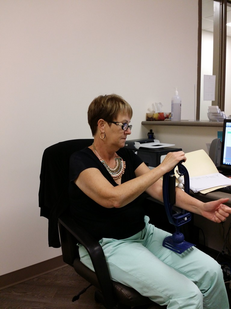 Woman stretching at desk at Oakville's Palermo Physiotherapy and Wellness to prevent injury and pain.