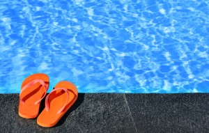 Flip flops by an Oakville pool. Keep feet wart free with foot clinic and chiropodist help in oakville.