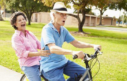 Seniors riding bikes in park showing Oakville Physio
