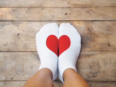 Selfie feet wearing white socks with red heart shape - showing oakville foot clinic, halton footcare