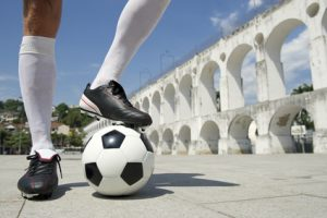 Soccer player standing on soccer ball showing sports physio in Oakville