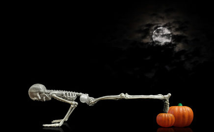 Halloween skeleton doing pushups on a pumpkin under a nice night time moon covered with dark clouds. showing an oakville Physio clinic