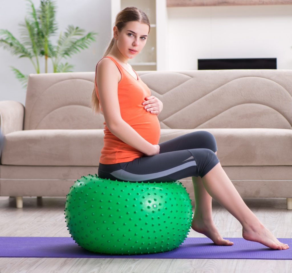 Pregnant woman on an exercise ball, prenatal exercise and therapy