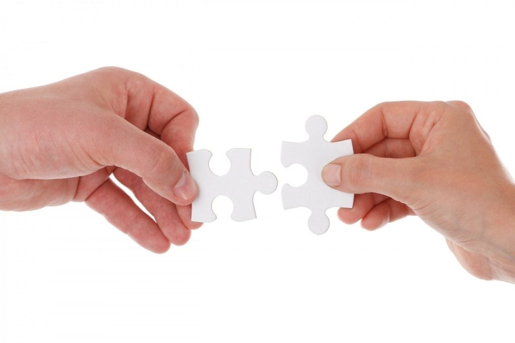Image depicts hands holding puzzle pieces to illustrate that medical imaging is only part of the diagnosis and hardly ever tells the whole story, in a blog by Oakville Physio discussing the pitfalls of imaging.