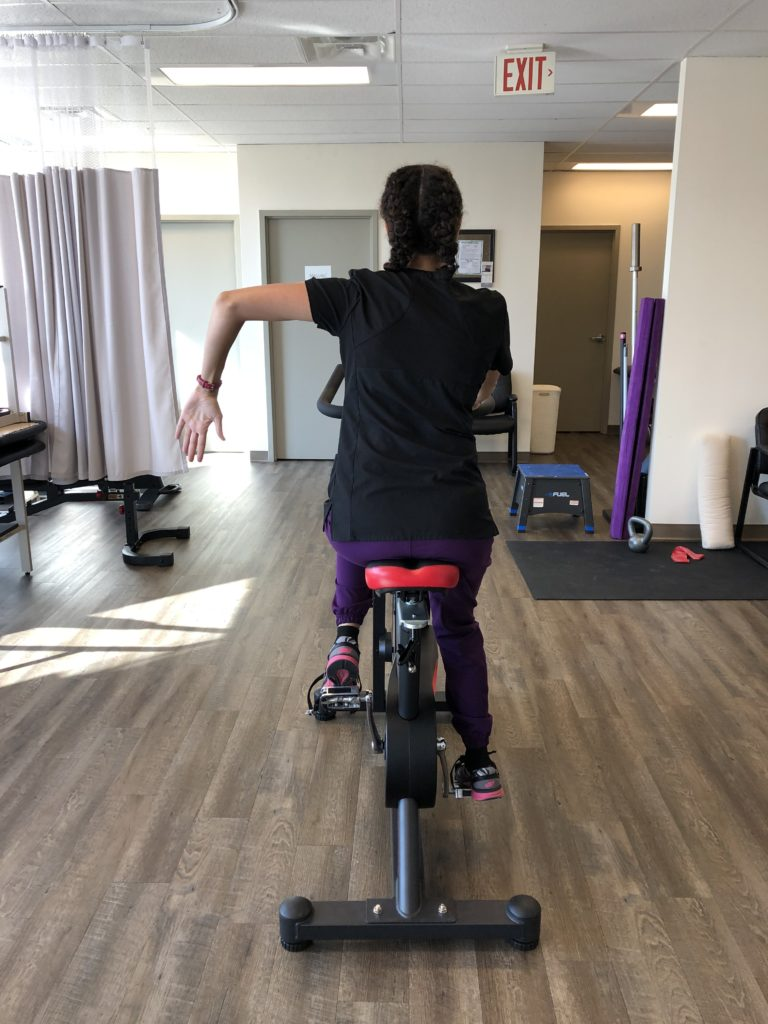 Oakville physio demonstrating stop hand turn signal for cyclists in bicycle safety and helmet blog